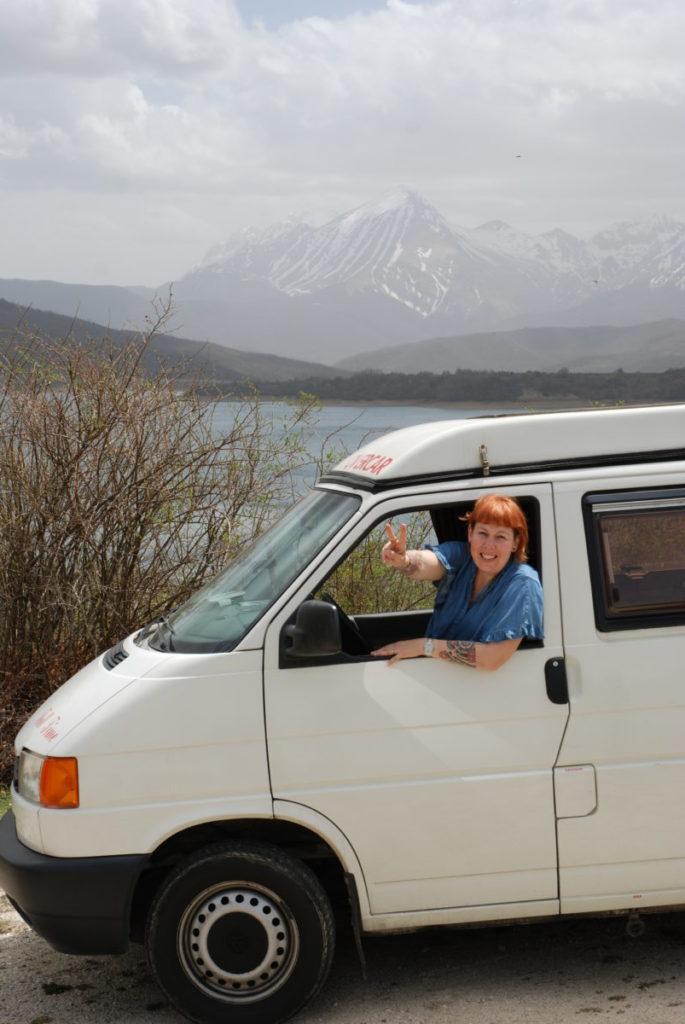 Anna su Tony Furgony in partenza, sullo sfondo il lago di Campotosto e il Gran Sasso