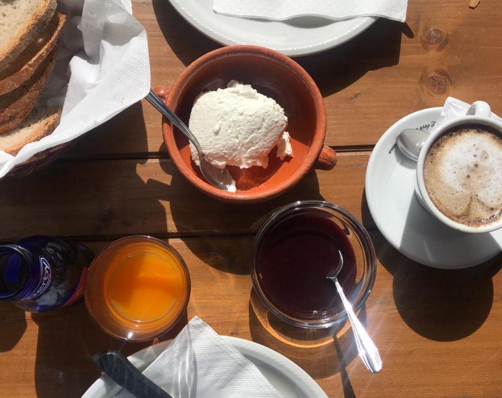 Colazione con ricotta di pecora, marmellata, pane e cappuccino